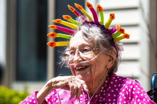 "Jeanne Kuentzel smiles while wearing a crown that reads, ""Happy birthday,"" while she celebrates her 100th birthday with family members and Oaknoll staff, Friday, May 8, 2020, at Oaknoll Retirement Residence in Iowa City, Iowa."