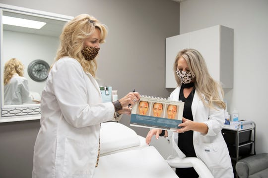 Tracy Alford, RN and owner of the Bloom Medspa shows Jackie Hopper, RN Aesthecian, look over the notes and diagrams at the Bloom Medspa in Jackson, Tenn., Thursday, May 7, 2020.