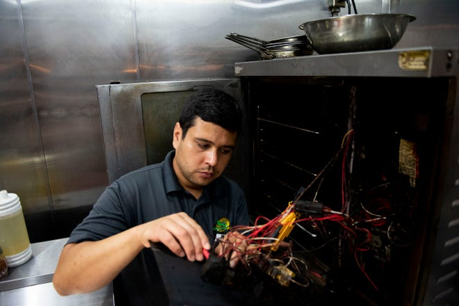 Juan Escobar, a technician with Alligator A & E Restaurant Equipment Repair, works on properly wiring a kitchen equipment at Flatiron Grille in Jackson, Tenn., Friday May 8,, 2020.