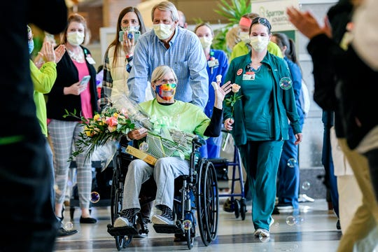 Jeannine Thelen waves to staff as she is treated to a parade in the lobby after being discharged as Sparrow Hospital's first COVID-19 patient on Friday, May 8, 2020, in Lansing.