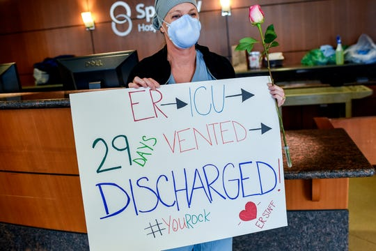 Jessica Carpenter, an emergency room nurse, holds up a sign and a flower for Jeannine Thelen who was treated to a parade in the lobby after being discharged as Sparrow Hospital's first COVID-19 patient on Friday, May 8, 2020, in Lansing.