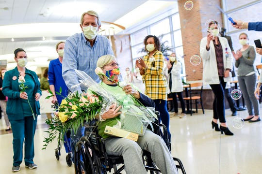 Jeannine Thelen is overcome with emotion as she is treated to a parade in the lobby after being discharged as Sparrow Hospital's first COVID-19 patient on Friday, May 8, 2020, in Lansing. Jeannine's husband Larry pushed her in a wheelchair along the parade route.