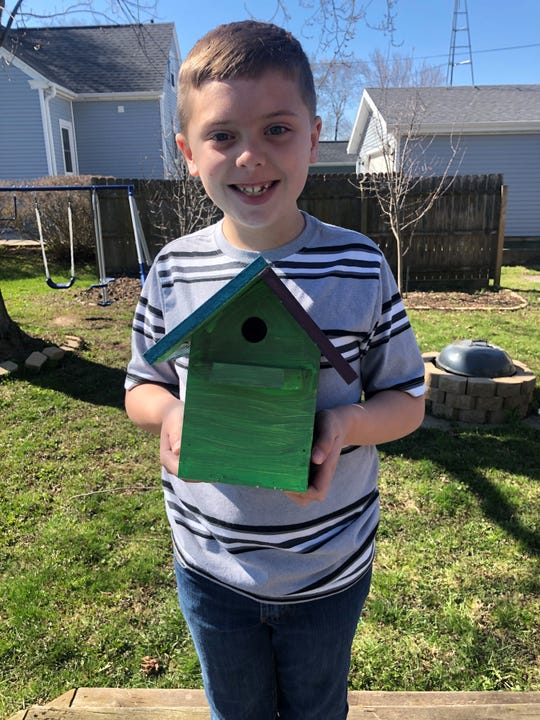 A second grade student at Franklin Elementary shows off his painted birdhouse which was donated by the grandfather of his teacher.
