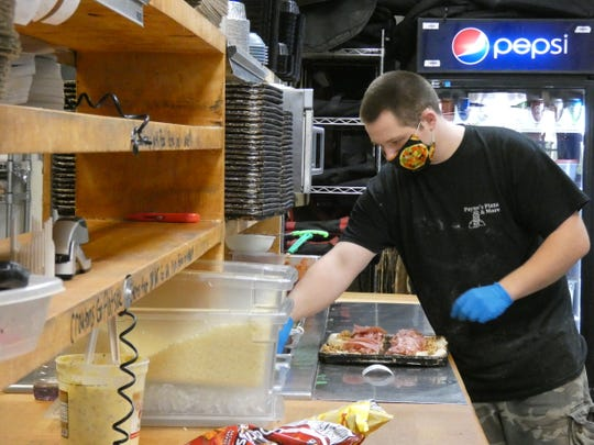 Brandon Jones wears a mask at Payne's Pizza while making a sandwich Friday. Payne's Pizza plans to open to dine-in customers on May 21, with changes to the dining room layout to allow for social distancing.