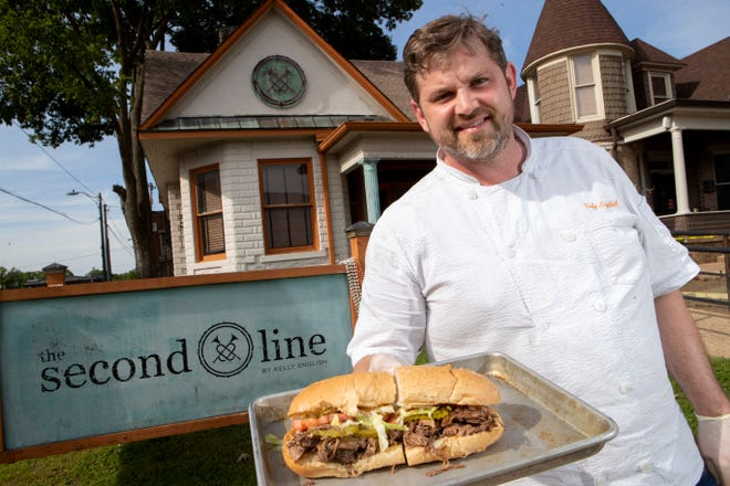 Chef Kelly English holds out a roast beef Po' Boy in front of his restaurant, The Second Line in Overton Square.