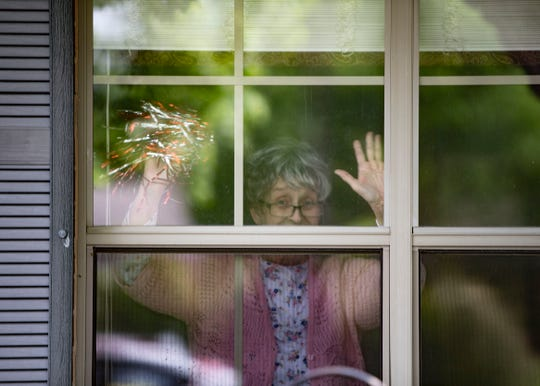 A Landmark of Desoto Nursing Home resident waves from her window during the MotherÕs Day parade in Horn Lake, Miss., on Friday, May 8, 2020. Due to COVID-19 residents canÕt be with their families.