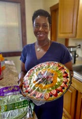 A slimmed-down Bridgett Wilder holds a fruit pizza created by fellow dietitian Angie Wilkes Tate at one of her nutrition classes.