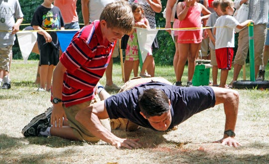 Sam Ryan watches his dad, then-U.S. Rep. Paul Ryan (R-Janesville), try to get his frog to jump during the Wisconsin State Frog Jump at the 2014 Dousman Derby Days. The 2020 frog jump has been canceled, along with the entire Dousman Derby Days event, because of the coronavirus pandemic.