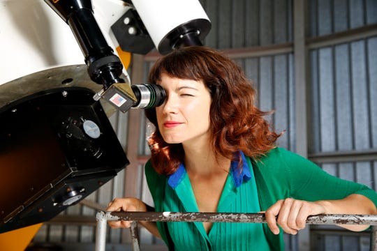 Lucianne Walkowicz looks at solar flares on the sun through a telescope at the Adler Planetarium's observatory in Chicago in 2015. The astronomer is suing the maker of American Girl dolls, alleging the Wisconsin company stole Walkowicz's likeness and name to create its space-loving doll.