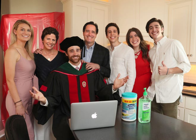 John Kopriva, center in cap and gown, is graduating from UW-Madison's medical school as an MD. At home with his family in Wauwatosa, they will be watching the graduation speeches on a laptop on the kitchen island while having brunch and celebrating the event.  From left to right are his girlfriend Hailey Rowen, mother Angela, graduate John, father John, brother Joe, sister Katherine and brother David.