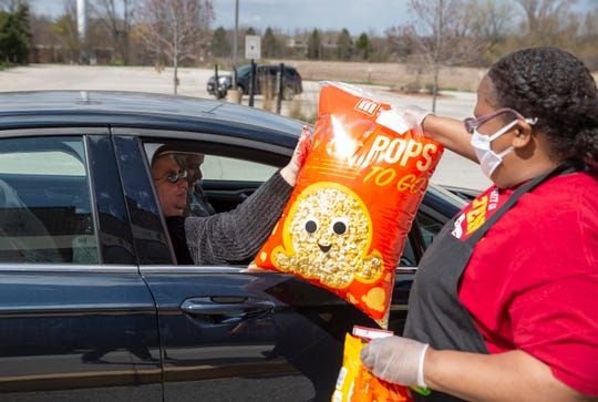 Marcus Theatres' Robin Cawthorn, right, hands popcorn to customer Lori Marx on Friday at Marcus North Shore Cinema in Mequon. Marx and her husband, Jerry Marx, came to pick up popcorn together, and they said they were going to watch a movie at home later.