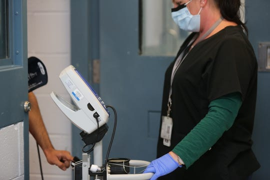 A nurse at the Doña Ana County Detention Center checks the vital signs of a detainee being housed in a negative pressure cell on Friday, May 8, 2020.