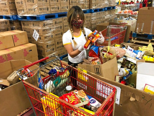 Volunteer Abigail Gold sorts food at Roadrunner Food Bank in Albuquerque, New Mexico, on Thursday, May 7, 2020, so it can be packaged and distributed to food pantries through the region as demand escalates. Gold is among the more than 133,000 New Mexicans who have had their unemployment claims processed by the state since mid-March. She said she wanted to help after being out of work for more than a month.