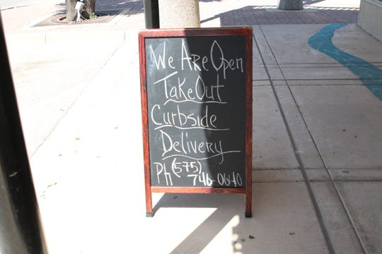 A sign at the Wellhead Restaurant and Brewpub indicates they are open for business in downtown Artesia on May 8, 2020.