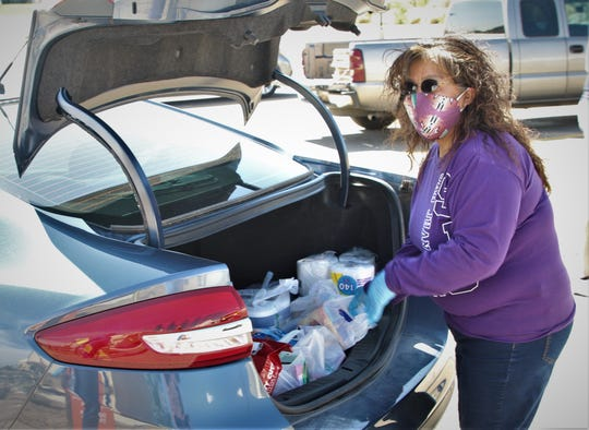 Shirley Hoskie, the operations coordinator for the San Juan College physical plant, prepares to unload a trunkful of goods May 8 on the college campus during a donation drive for people on the Navajo Nation struggling from the COVID-19 shutdown.