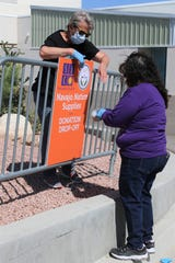 Volunteers Laura Darrow, left, and Shirley Hoskie, both employees of the San Juan College physical plant, post a sign May 8 on the college campus alerting drivers of the drop-off site for donations for Navajo Nation people affected by the COVID-19 shutdown.