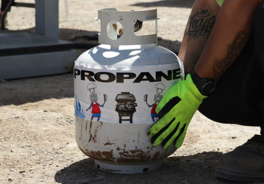 A propane tank is fitted on May 8 with a sleeve during the free propane refill service by Navajo Nation Oil and Gas Company and Nations Gas Technologies Inc. in Sanostee.