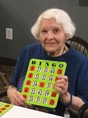 Betty Hamilton, a WWII veteran, with a bingo card at American House senior living community in West Bloomfield.