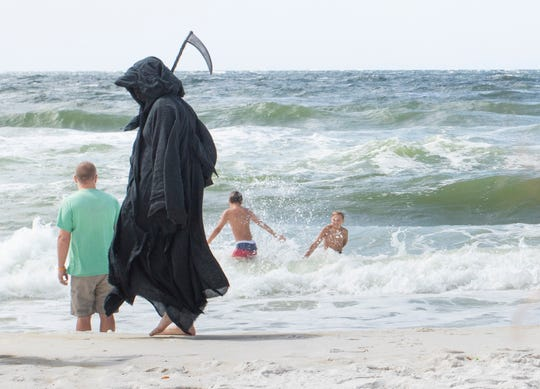 Daniel Uhlfelder, of Santa Rosa Beach, walks past people frolicking in the water at Pensacola Beach dressed as the Grim Reaper on Friday, May 8, 2020.  Uhlfelder wants the public to know that he doesn't believe that it is safe for people to return to the beaches during the coronavirus pandemic.