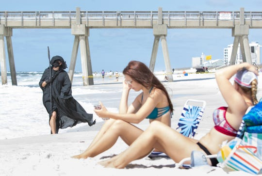 Daniel Uhlfelder, of Santa Rosa Beach, left, walks along Pensacola Beach dressed as the Grim Reaper on Friday, May 8, 2020.  Uhlfelder wants the public to know that he doesn't believe that it is safe for people to return to the beaches during the coronavirus pandemic.