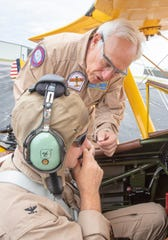 Roy Kinsey, top, straps Capt. Timothy Kinsella, commanding officer of NAS Pensacola, into his vintage Stearman biplane before taking off from Pensacola International Airport on Friday, May 8, 2020.  Two Stearmen planes flew over Pensacola, including Veterans Memorial Park, in honor of the 75th anniversary of WWII's Victory in Europe Day.