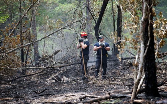 Alec Morrow and Lt. Frank Donohoo from the Skyline Fire Department monitors a wooded area off Garcon Point Road for hot spots on Friday, May 8, 2020.