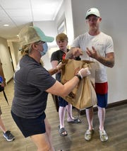 Julie White, with Santa Rosa County, gives the Dunlavey family a care package at the Hampton Inn in Navarre on Friday, May 8, 2020. The Dunlaveys are among the displaced families staying at the hotel due to the Five Mile Swamp Fire in Milton.