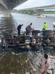 A dump truck ran through a guardrail on I-10 and toppled into the Blackwater River on Friday not longer after the stretch of interstate reopened following its closure due to the Five Mile Swamp Fire.
