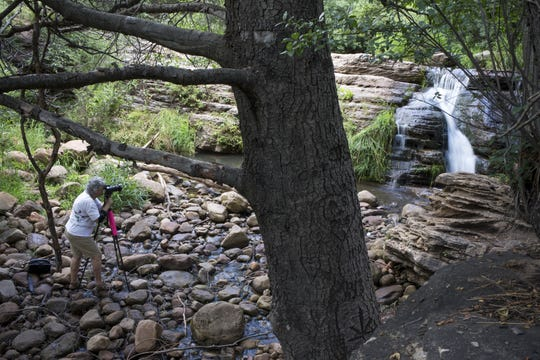 Katalin Hollay, of Phoenix, photographs a waterfall at Tonto Creek on July 29, 2014.