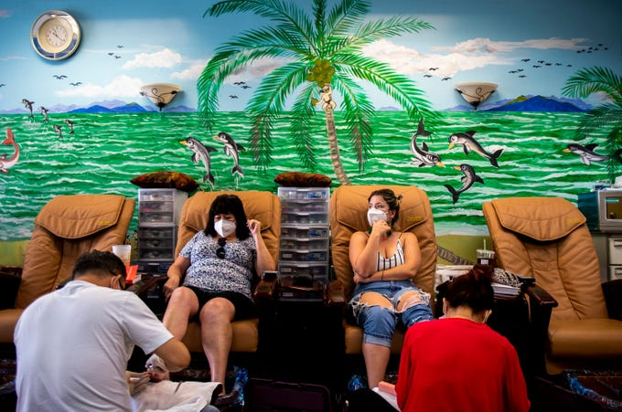 From left, manager David Grady and owner Mimi Nguyen do mother and daughter customers Tonna and Elaina Yutze's nails at AZ Nails Spa 101 near the P83 Entertainment District in Peoria on May 8, 2020.