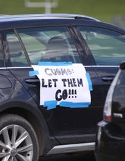 Signs posted on cars near a graveside vigil at the prison burial ground at Fishkill Correctional Facility in Beacon on Thursday, May 7, 2020.