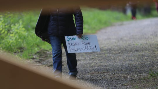 A protester carries a sign at a graveside vigil at the prison burial ground at Fishkill Correctional Facility in Beacon on Thursday, May 7, 2020.