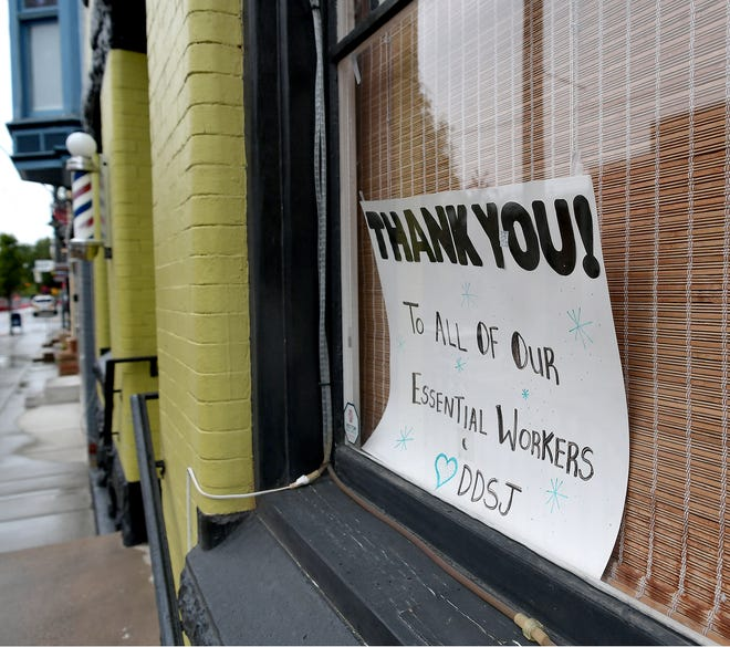 A poster heralds essential workers in the window of Di Di & Smiling John's Barber Shop in York City Friday, May 8, 2020. According to a consultant's report on York County's economic future, up to 30% of local businesses may have to shut their doors permanently. Bill Kalina photo