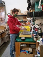 Food stores have adapted in many ways during the coronavirus pandemic. Here, Chris Cellucci of Hollabaugh Bros., Inc. wraps asparagus in plastic to sell to the public. The store is not selling loose asparagus during the pandemic.