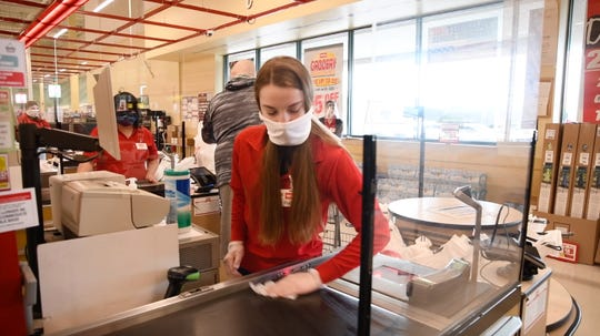 A Weis employee sanitizes a conveyor belt to help prevent the spread of the novel coronavirus. Stores have taken a number of steps to keep employees and customers safe during the pandemic.