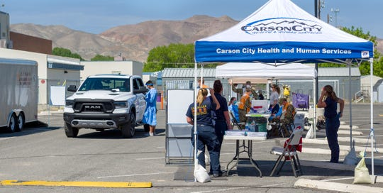 COVID-19 testing is performed in a drive-thru clinic at Yerington High School.