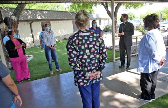 Bishop Michael J. Sis, right, conducts a blessing of the nurses ceremony at Arbor Terrace Nursing Home in honor of National Nurses Week on Thursday, May 7, 2020.