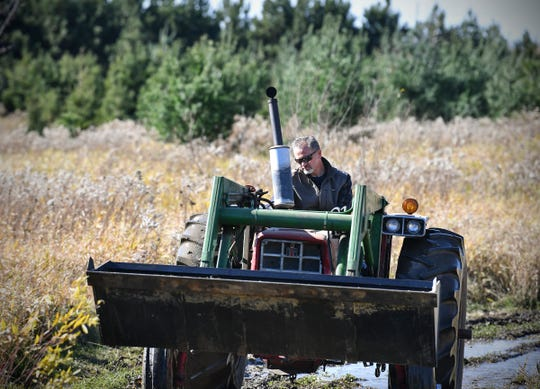 Billy Dinkel drives a tractor through wet ground Saturday, Oct. 26, 2019, on land he owns near Long Prairie.