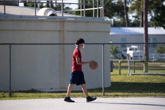 Jordan Fierrof, 15, wears a mask given to him by Marybeth Peña, nurse program specialist with the Martin County Department of Health, on Thursday, May 7, 2020, at St. Lucie Mobile Village near Indiantown in Martin County. Peña, who is part of a group of Department of Health staff handing out about 4,500 cloth masks donated by Cleveland Clinic Martin Health, recently produced a video in English and Spanish to educate children and families about healthy habits and germ prevention and has provided health education in the Indiantown community since 2015.