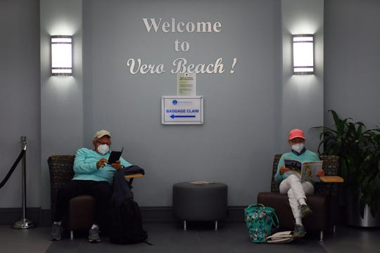 Jim Tarsetti (left) and Penny Seavey read in the waiting lounge at the Vero Beach Regional Airport on Friday, May 8, 2020, as they wait to board an Elite Airways flight to Portland, Maine. Friday's flight is the first flight out of Vero Beach for Elite Airways after having to cancel flights in March and April because of the coronavirus outbreak and settling debts with the city for overdue bills.