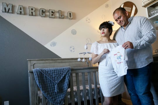 """Marcos and Valerie Garcia hold a onesie that reads, """"hand picked for earth by my brother in heaven,"""" at their home Thursday, May 7, in El Paso. The Garcias lost their first child, Marcelo, to SIDS in December of 2019. They found out they were pregnant again in early March. The Garcias suffered a tremendous loss but said that they believe Marcelo will watch over their family as they continue to grow."""
