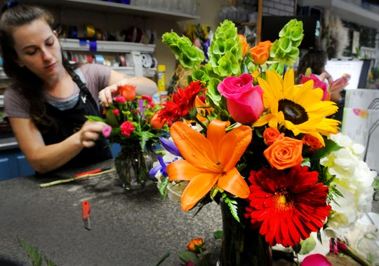 Megan McCarthy, designer for The Growing Co. in Ventura, helps prepare orders for Mother's Day. Florists were allowed to reopen with limited services this week.