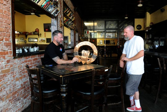 Clint Garman, left, owner of Garman's Restaurant & Irish Pub in downtown Santa Paula, holds a claddagh while talking with David Lippert, the business' landlord. Garman temporarily closed the pub in March due to COVID-19. He announced on May 1 that it is permanently closed for financial reasons caused by the pandemic.