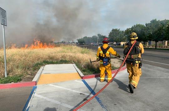 Visalia firefighters battle a grass fire along Cameron Avenue on Thursday, May 7, 2020.