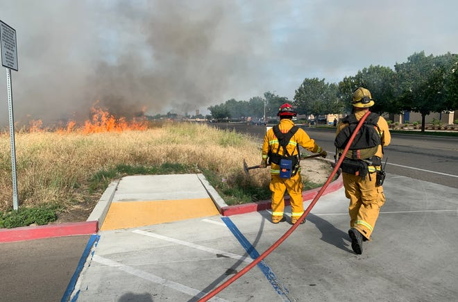 Visalia firefighters battle a grass fire along Cameron Avenue on Thursday, May 7, 2020.