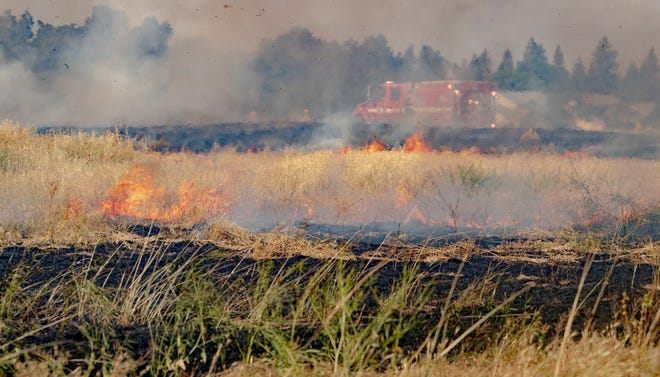 Visalia City and CAL FIRE firefighters work Thursday, May 7, 2020 to control a grass fire that eventually burned 22-acres in the lot north of Costco. Traffic was diverted away from Cameron about 5 p.m. for more than an hour while crews worked.