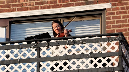 As she does every night after the 7 p.m. applause and pots and pans salute to health care workers, Rosemarie Castellano plays the violin from the terrace of her sixth floor New Rochelle apartment on May 7, 2020.
