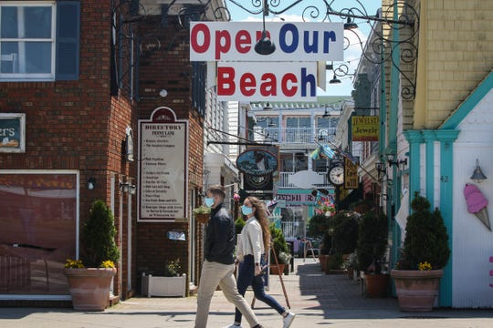 """Jesse Fisher and Jillian Robert pass under an 'open our beach' sign on their way to pick up food at Grotto Pizza on Rehoboth Ave. They don't agree with the message, """"the last thing we need is another outbreak,"""" said Fisher."""