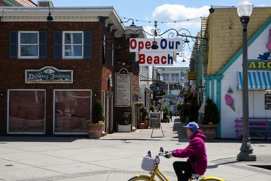 A biker passes in front of an 'open our beach' sign on Rehoboth Ave. The sign hangs over Penny Lane shopping center and was installed by owner Clint Bunting, who said he believes the beach should re-open for activities including walking, jogging and surfing.