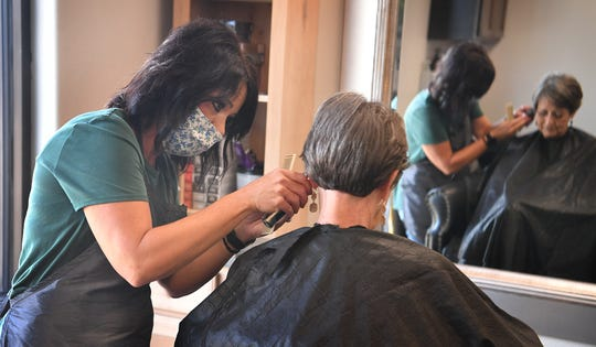 Charlotte Battista gets a haircut from stylist Melisa Glidewell at Serenity Salon Friday morning, the first day barber shops and hair salons were allowed to reopen during to the pandemic.
